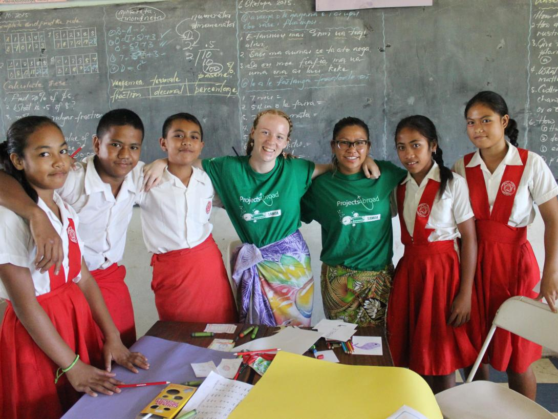 Students and a volunteer teacher take a photo on a summer volunteer program in Samoa.